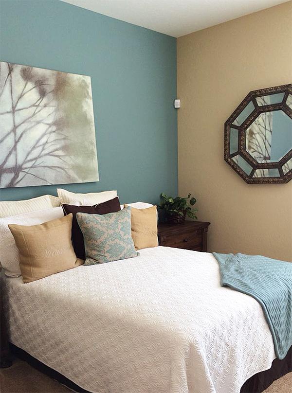 Duvarlardaki maviyi toprak tonlarıyla birleştiren bir yatak odası