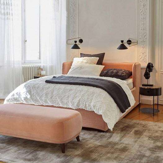 Un banco de terciopelo salmón para decorar el pie de cama