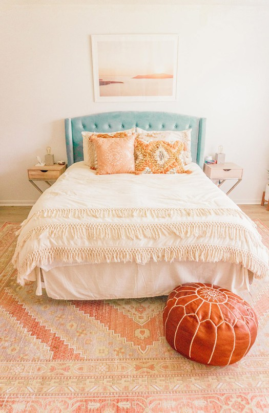 Pie de cama decorado con una alfombra y un puf