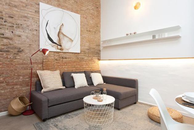 Çıplak tuğla duvarlı küçük bir oturma odası