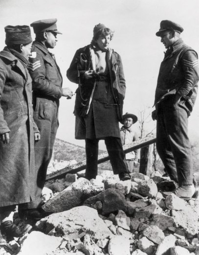 Black and white photograph of   Gellhorn in Italy during the Second World War - she stands on a pile of rubble in conversation with three other people.