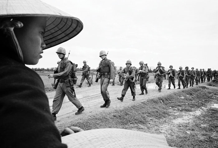Black and white photograph of soldiers on the road in Vietnam.