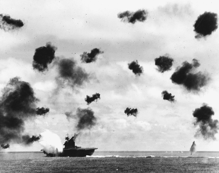 USS Yorktown was the target of two Japanese air-strikes. It is seen here at the moment of a torpedo impact.