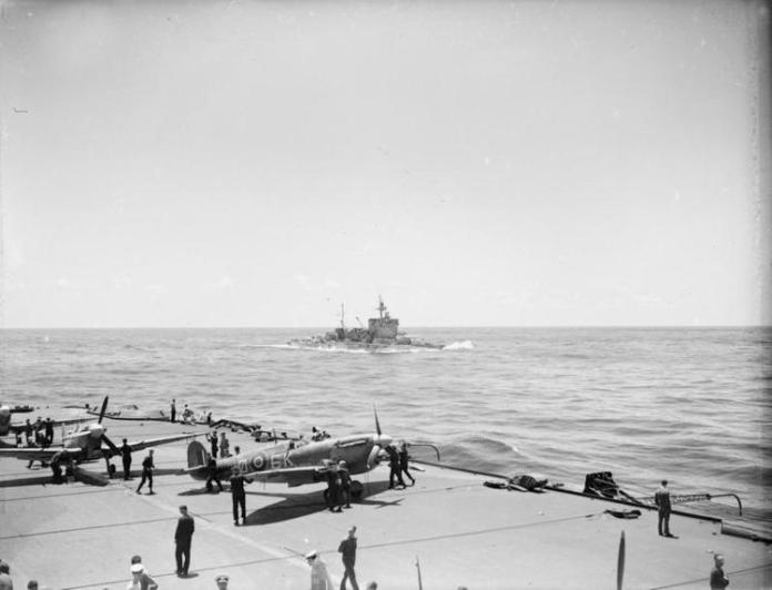 HMS WARSPITE, with Seafires of FORMIDABLE in the foreground, part of Force H in the Ionian Sea.