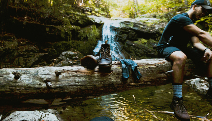 Image of hiker taking shoes off in forest