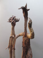 Uncertain couple, with a shy young girl, and a strong and hairy pretender, with arms and hands of crocodile Sculpture made with the front legs of a small stuffed crocodile from a flea market.