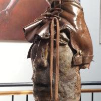 Pourquoi pas une chaussure en cuir en guise de casque pour ce soldat qui a l'habitude de marcher à pied ? Le visage a été réalisé en raku, et le casque a été confectionné avec une chaussure.