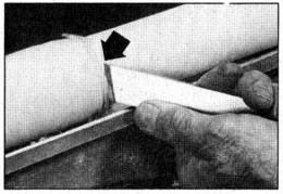 Utilice una cuchilla de filo oblicuo para cortar el cilindro a su tamaño. Realice el corte con la sección central de la cuchilla solamente. La punta (vea la flecha) no deberá hacer contacto