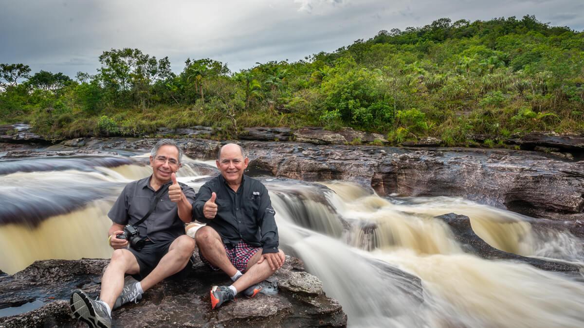 Dos fotógrafos mexicanos en Caño Cristales, sentados sobre una roca a orillas de un río con cascadas