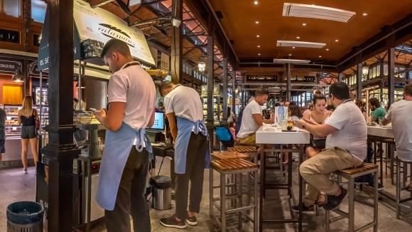 Turistas comiendo en mesas en el Mercado de San Miguel
