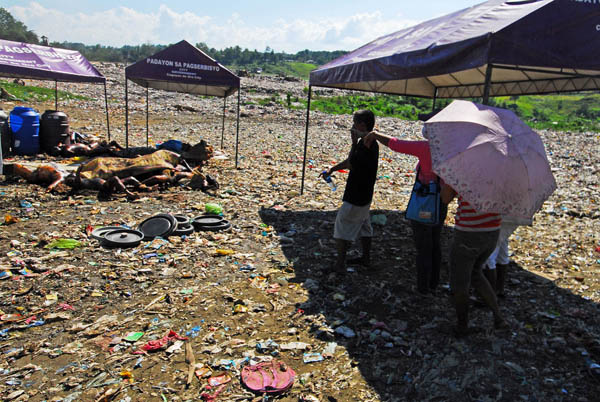 Relatives of missing residents of Cagayan de Oro view the bodies that were transferred from Bollozos Funeral Parlor in Barangay Bulua to the garbage landfill in Barangay Carmen on Monday, Dec. 19, 2011. The city government ordered their transfer Monday after the morgues were swamped with bodies killed by Tropical Storm Sendong. MindaNews photo by Froilan Gallardo