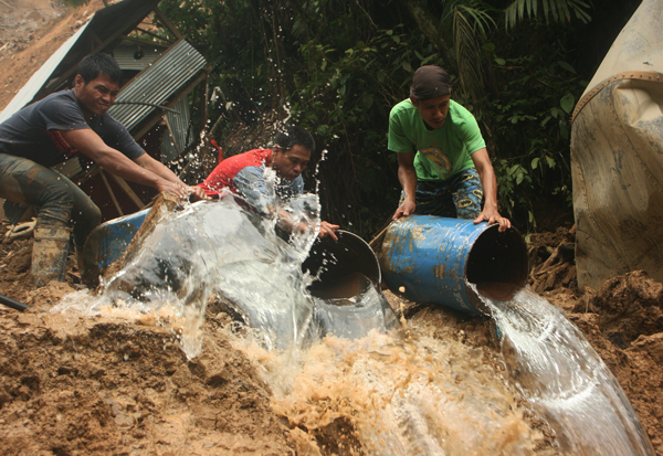 Concerned miners help in retrieval operations by flushing barrels of water to remove dirt at a landslide that hit Barangay Napnapan, Pantukan in Compostela Valley morning of January 5 killing at least 36 people. MindaNews Photo by Toto Lozano