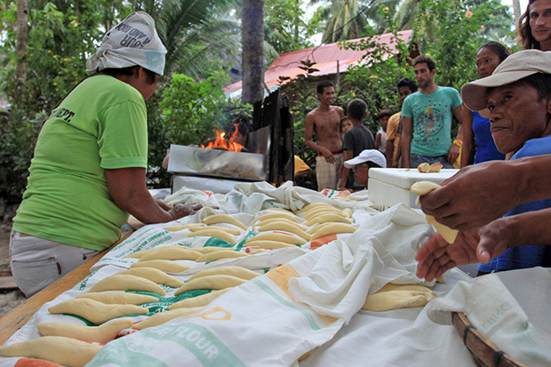 "FREE BREAD. Surfers and guests get a free taste of local bread called ""pan de surf"" at Cloud Nine in General Luna, Siargao Islands on Monday, September 23, 2013 during the opening of two International surfing competitions. MindaNews photo by Roel N. Catoto"