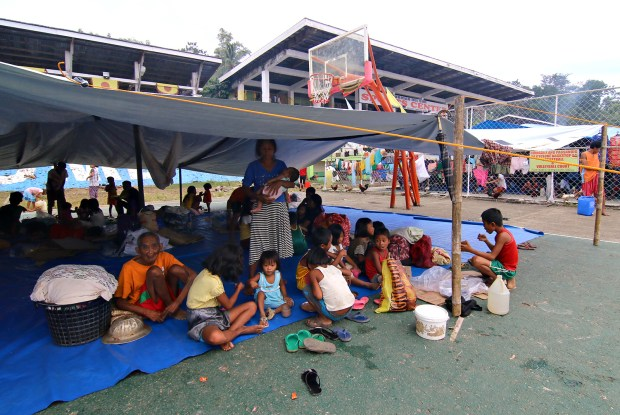 TENT BREAKFAST. Displaced villagers from barangay Diatagon, Lianga town in Surigao del Sur eat their breakfast under the tent at the sports center turned evacuation area in Tandag City, September 4, 2015. MindaNews photo by Erwin Mascarinas