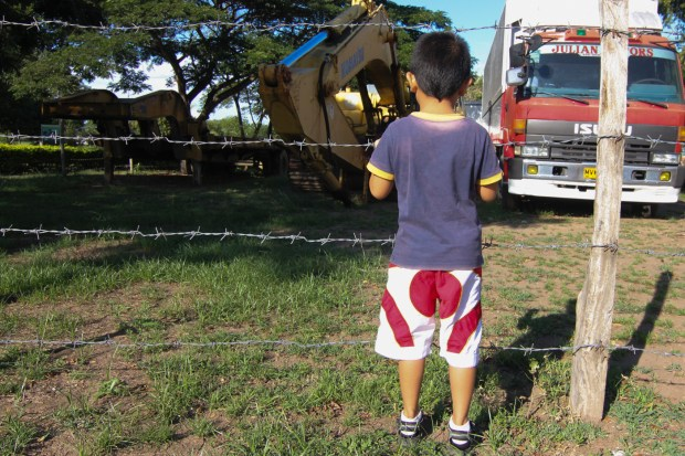 Ronnie Perante III, son of the Ronnie Perante who was one of the victims of Ampatuan massacre, looks at the backhoe and other vehicles that were used by perpetrators inside the PNP evidence yard at Tambler, General Santos City in this photo taken on November 21, 2015. MindaNews photo by Toto Lozano