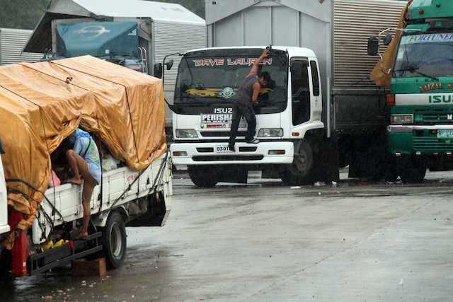 Crew members of cargo trucks secure their things while waiting for clearance to travel in  Lipata Port,  Surigao City on Friday afternoon, December 18, 2015. At least 119 rolling cargo vehicles have been stuck at the port since Thursday due to inclement weather. MindaNews photo by Roel N. Catoto