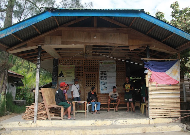 """A tattered Philippine flag hangs outside the headquarters of the Special CAFGU Armed Auxiliary (SCAA) in Barangay Demoloc, Malita, Davao Occidental in this photo taken on March 11, 2016. On these steps, Tagakolu farmer Orlando """"Kaido"""" Engo, his 15-year old son Jerome and 14-year old grandnephew were made to sit and bathed with iced water. The tattered flag was removed after MindaNews told the officer-in-charge that they should replace the flag. The Flag and Heraldic Code provides that flags that begin to show signs of wear and tear """"shall be replaced immediately."""" MindaNews photo by TOTO LOZANO"""