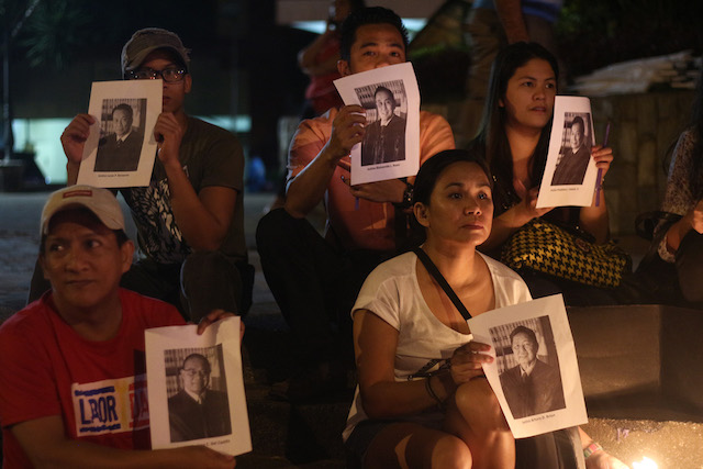 Members of Konsensya Dabaw show photographs of the 15 Supreme Court justices during the candle-lighting vigil in Davao City on Monday night, ahead of the anticipated Supreme Court ruling on Nov. 8 on the Marcos burial at the Libingan ng mga Bayani. Mindanews photo