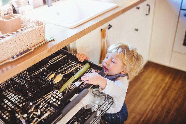 Child climding up dishwasher