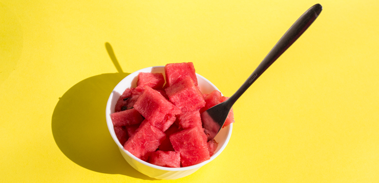 pieces watermelon in bowl with fork, yellow background