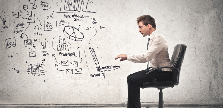 man at desk with illustrated laptop and brainstorming charts, etc.