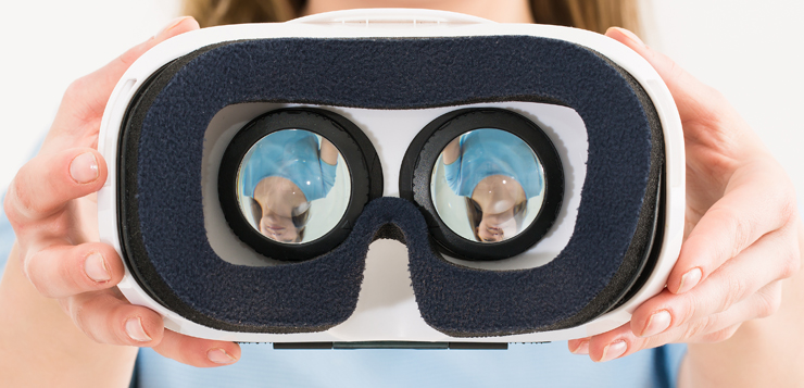 woman holding up virtual reality glasses