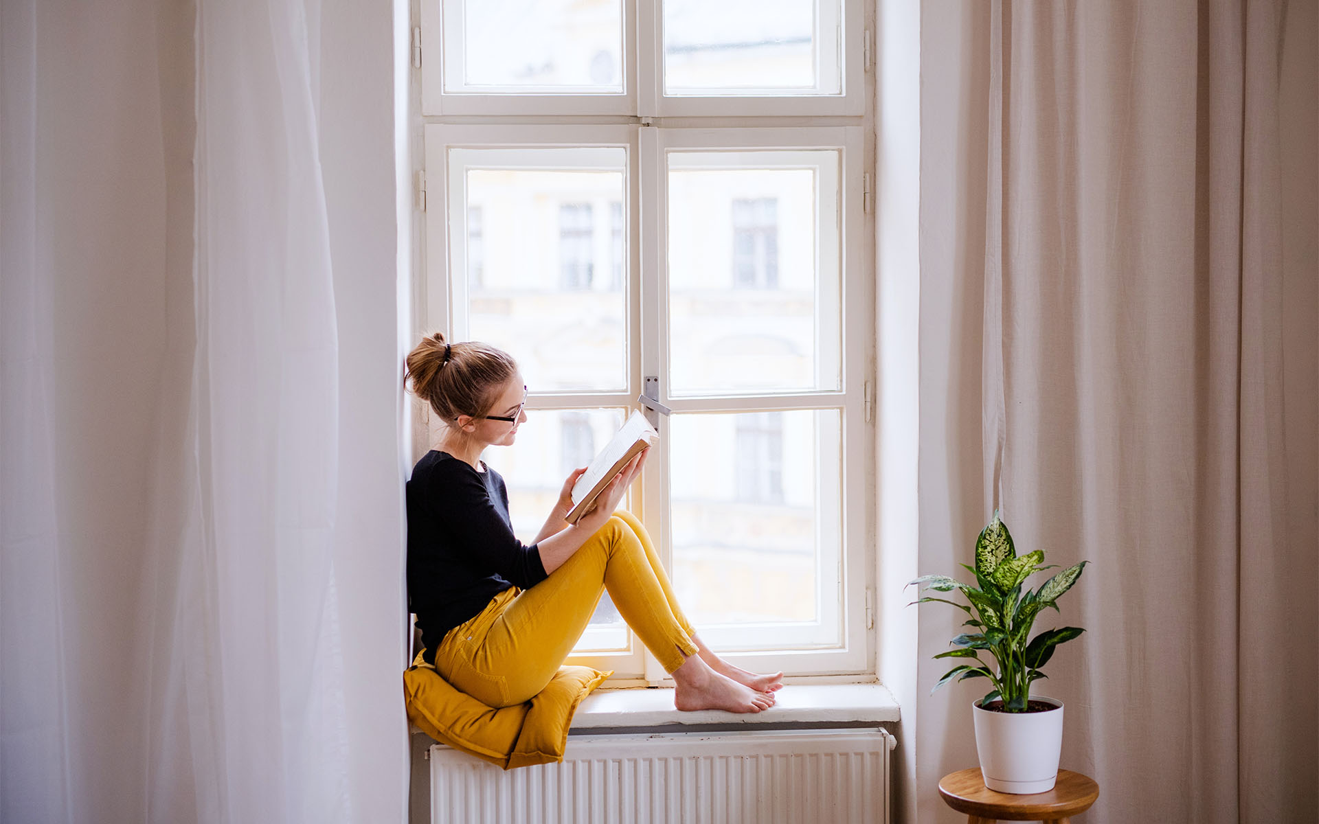 6 Mindful Books to Keep Your Mind Healthy_Woman Sitting on Windowsill Reading a Book