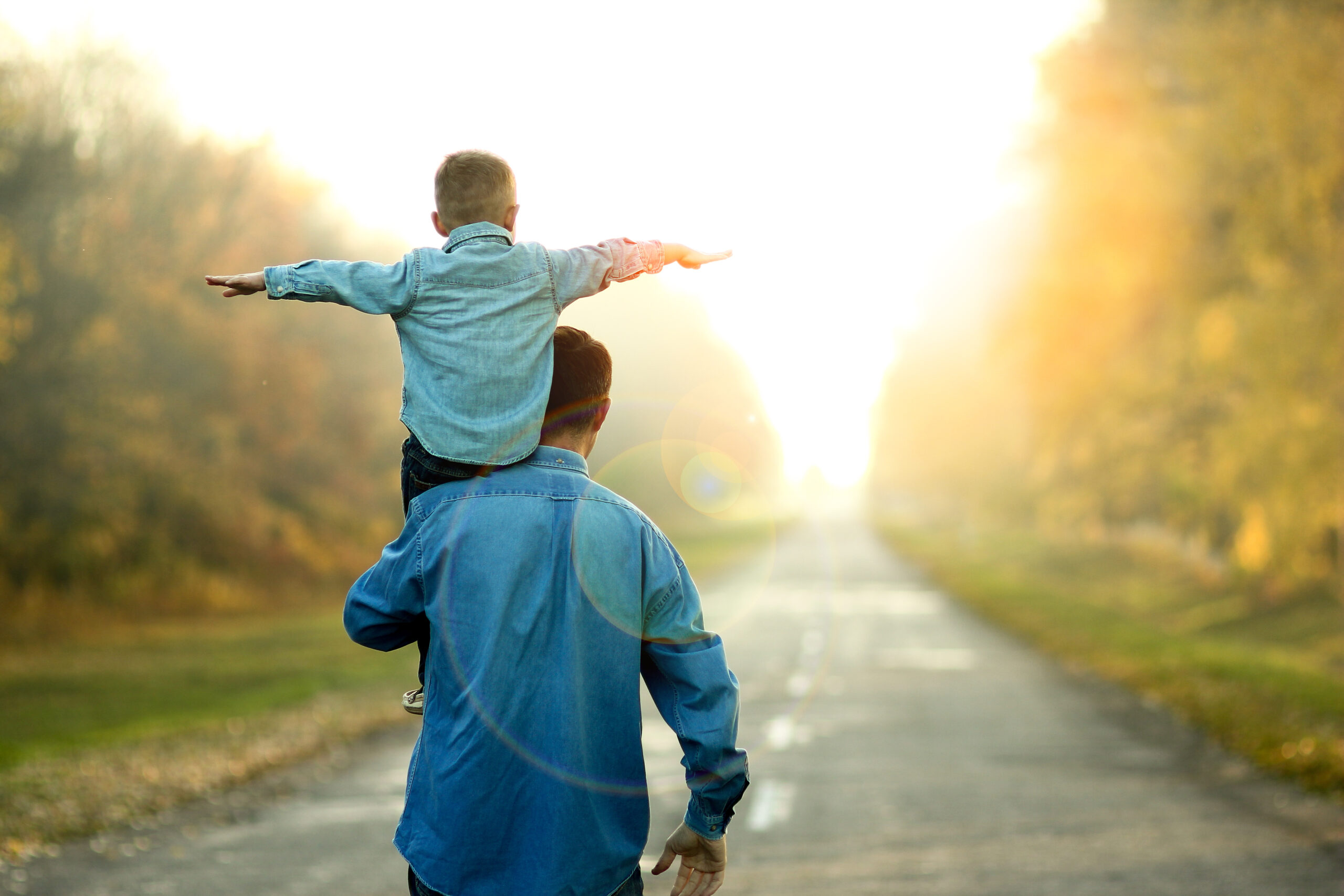 Man holding a child on his shoulder. The child has both arms stretched out as they walk down a road towards a setting sun