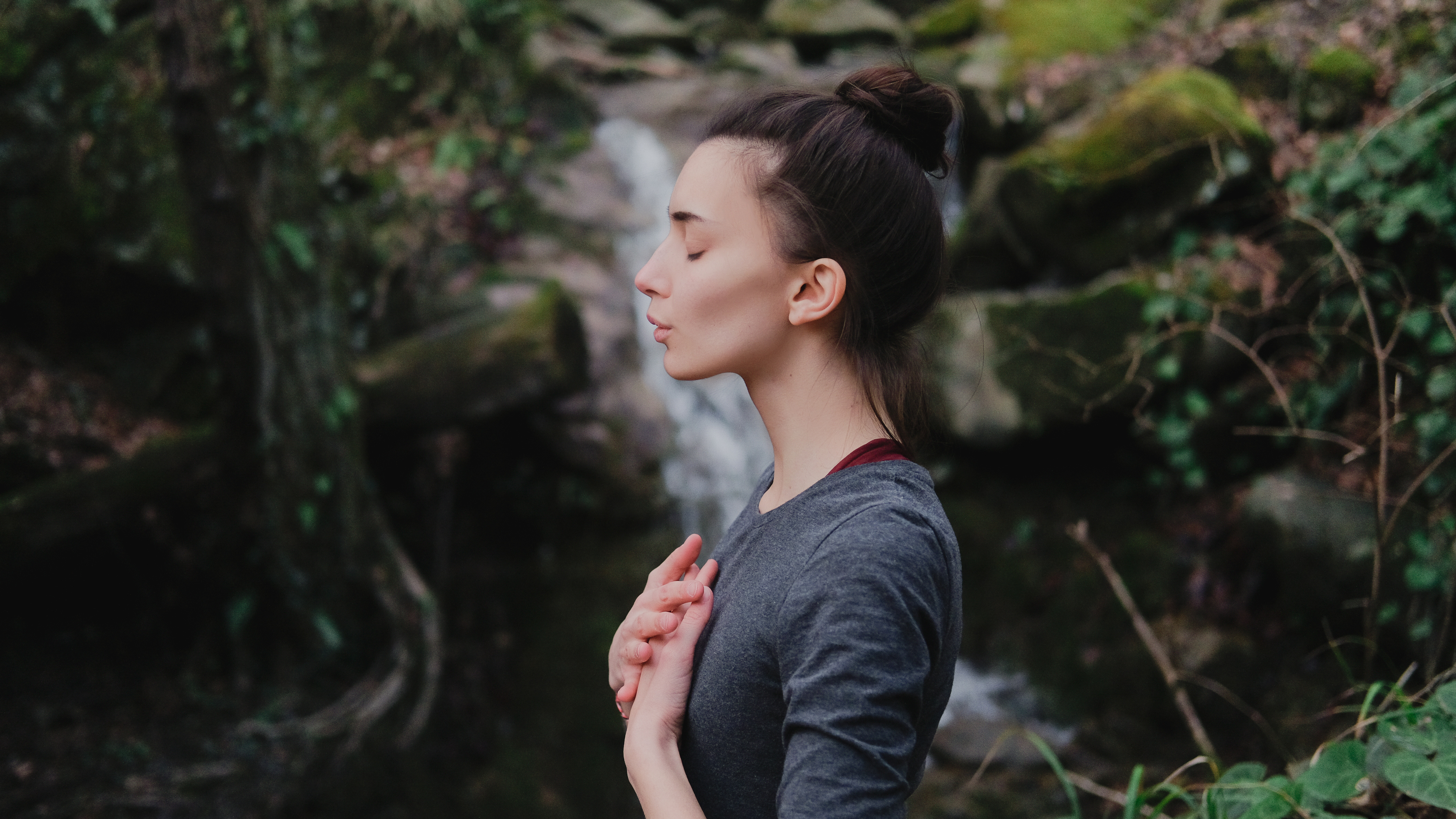 Is Breathing Connected to Free Will? - Woman breathing with eyes closed and hands on heart