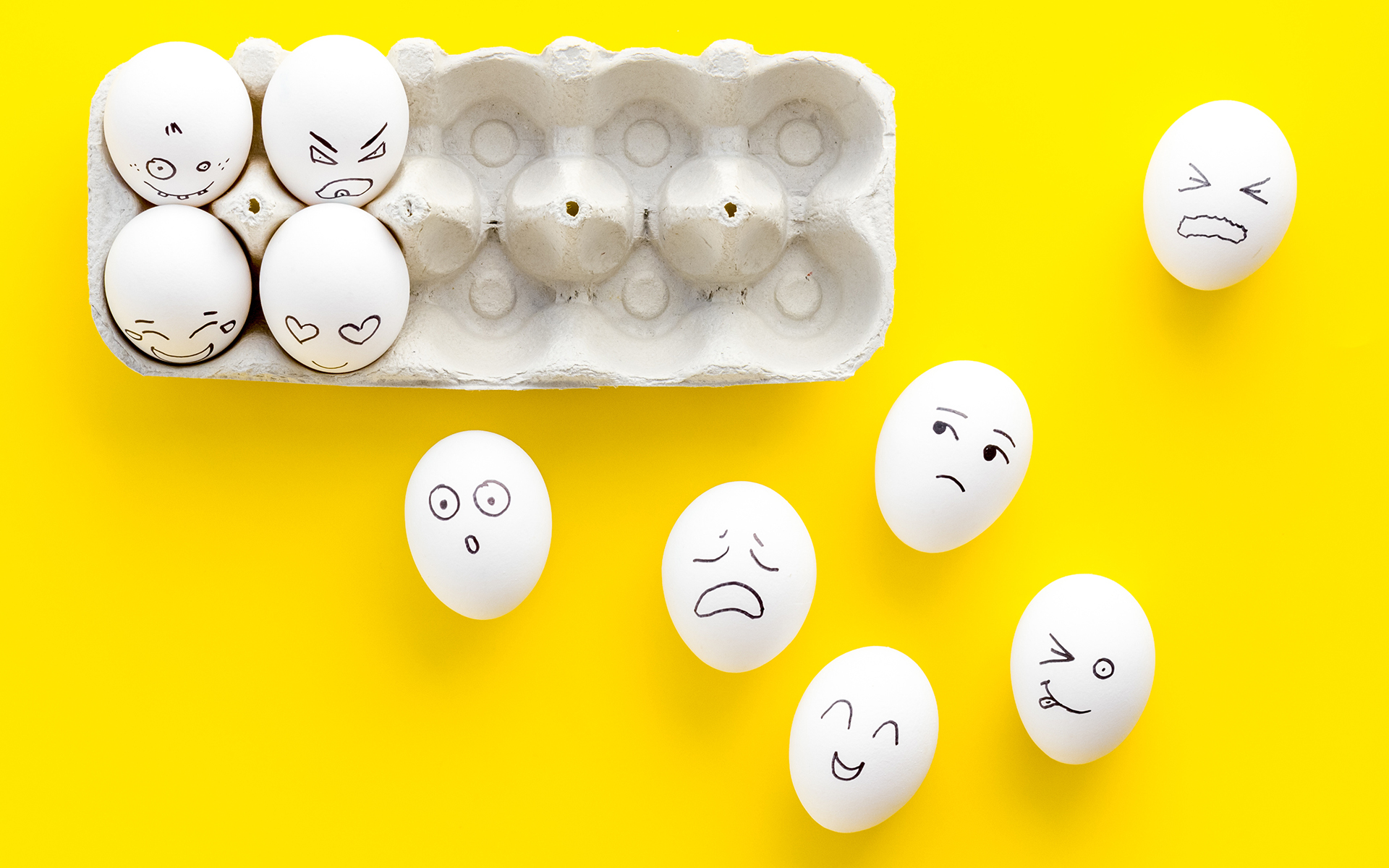 Emotions in communication at social media. Faces drawn on eggs. Yellow background top view