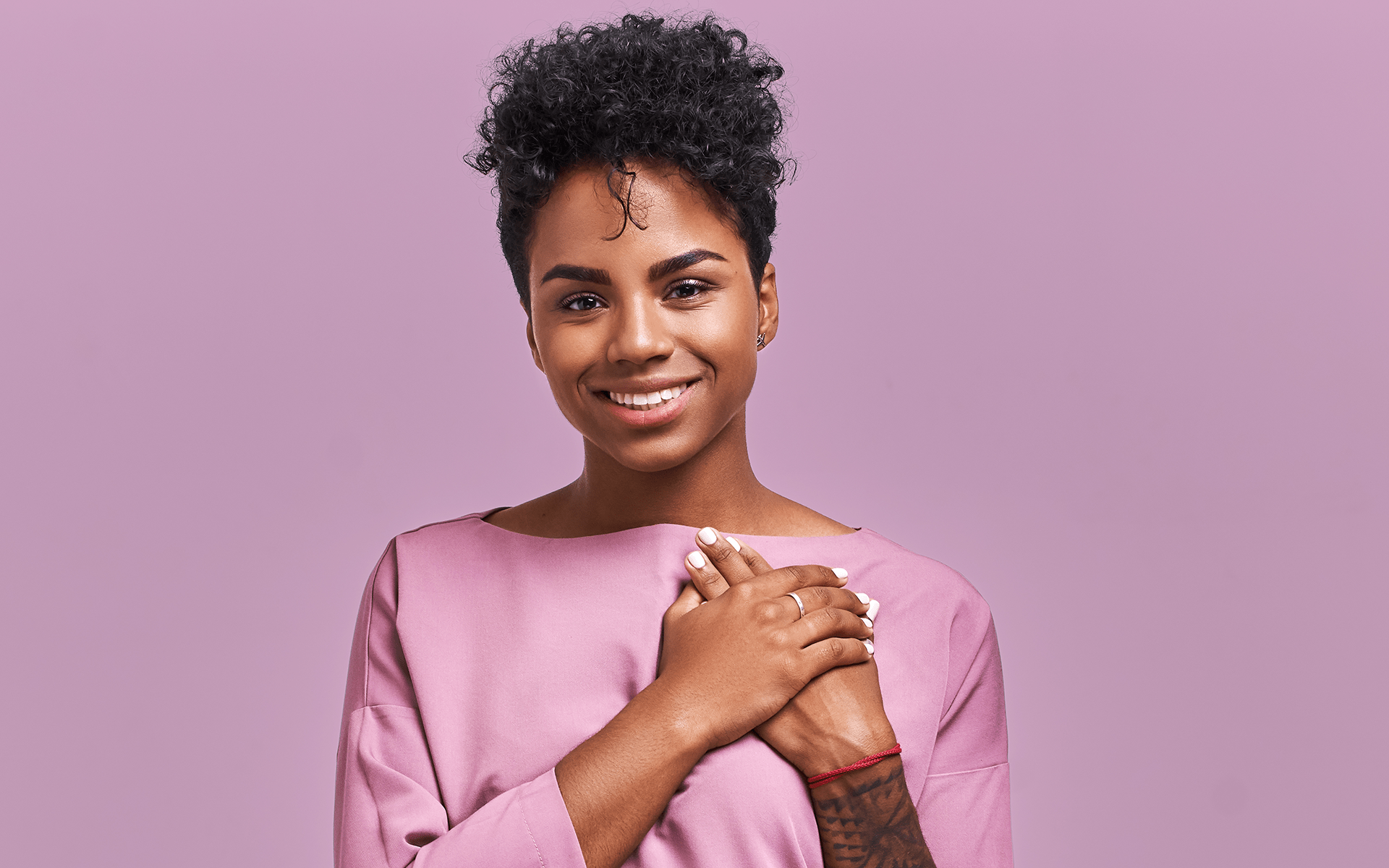 Studio image of a Black women smiling at the camera with her hands on her chest. She's wearing a back shoot with a lavender background behind her.