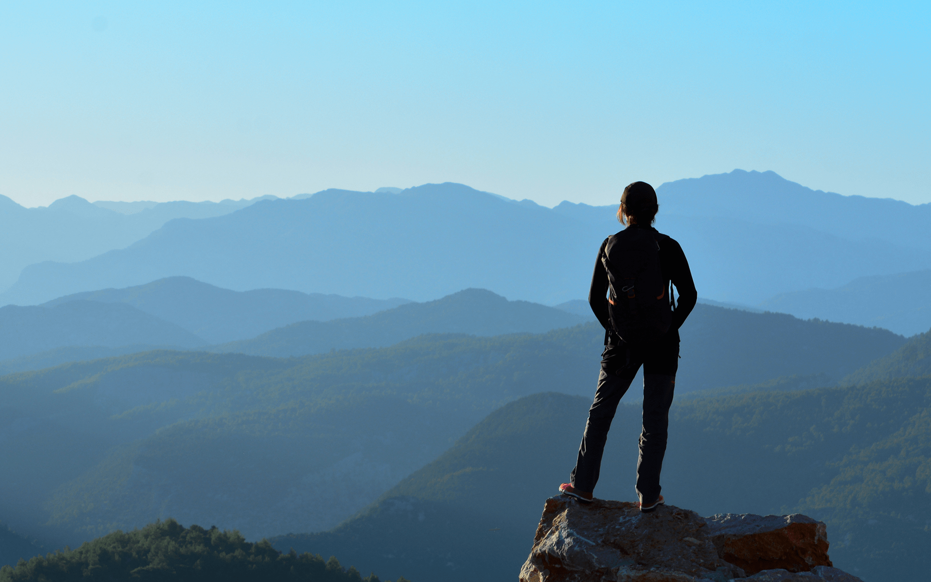 Let Go of Stress and Welcome Wisdom—A woman stands on a mountain peek looking out over layers of mountains in the distance.