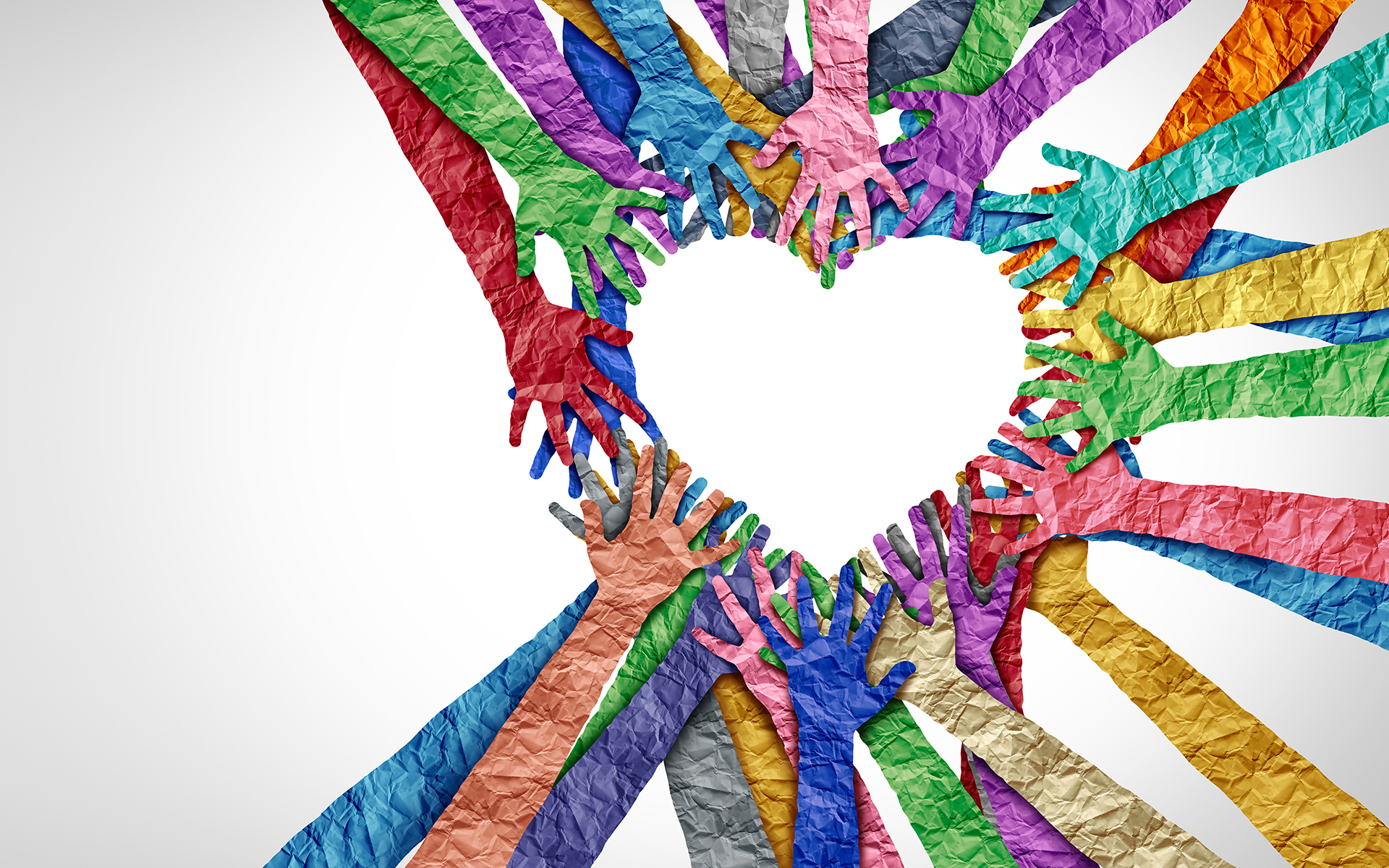 Colorful, crumbled paper hands forming a heart