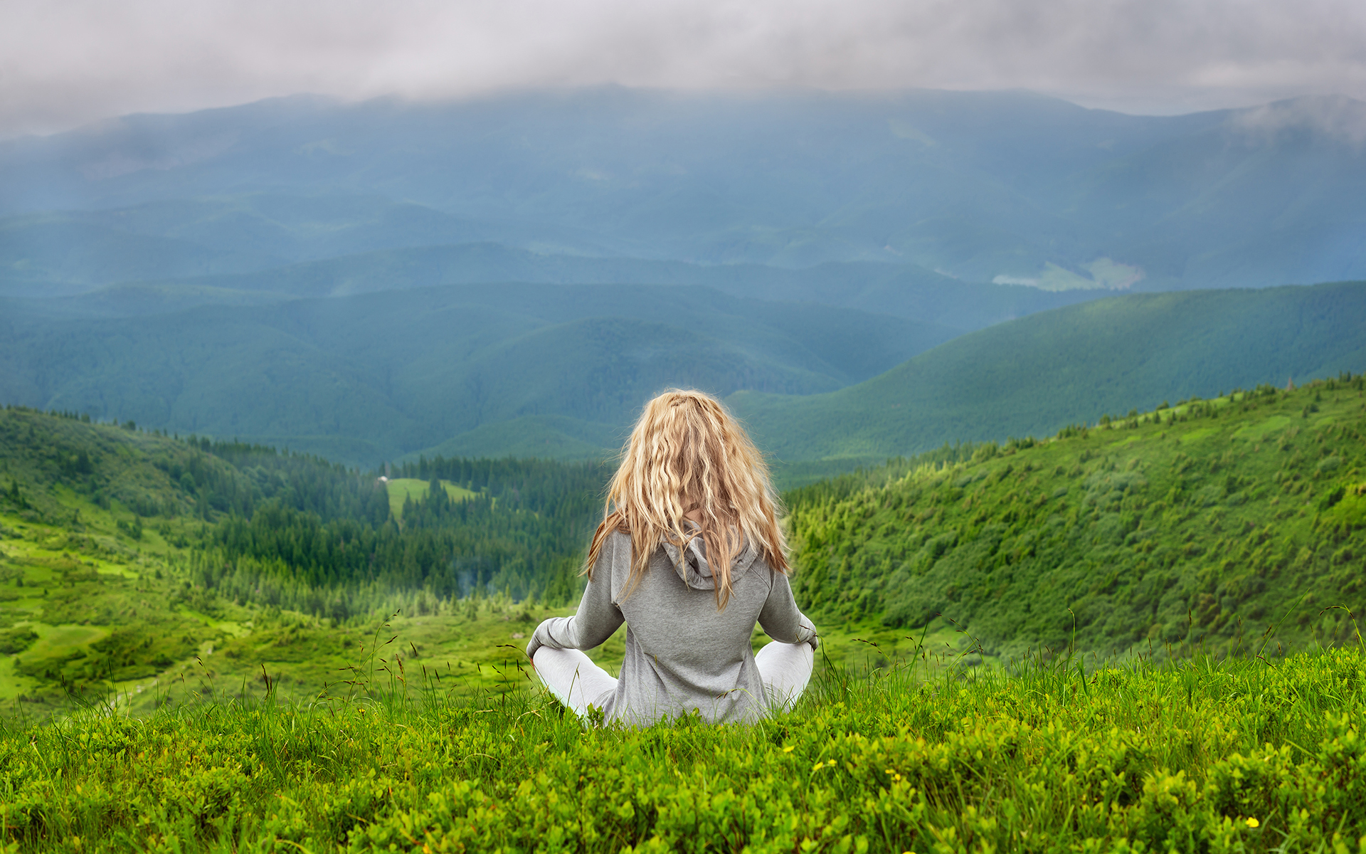 New research on mindfulness meditation: June Issue 2020 - Woman sitting in mindfulness meditation in the Carpathian mountains.