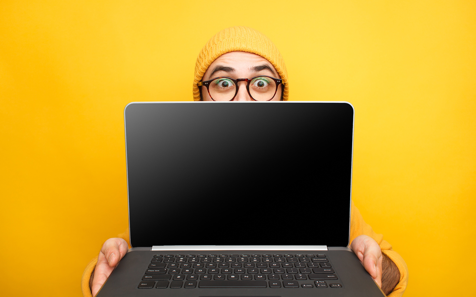 Can text be used for the greater good? - Expressive young man in glasses giving innovative laptop making presentation on yellow.