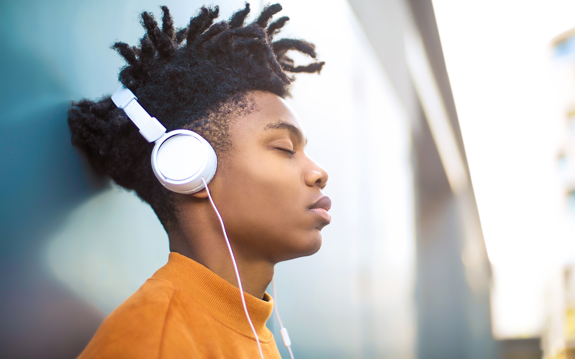 A Guided Meditation for Patience and Resolve - Young Black man listening to a guided meditation with white headphones