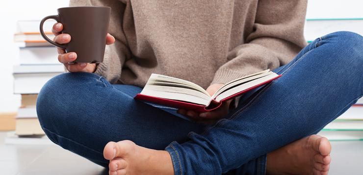 woman sitting cross-legged reading
