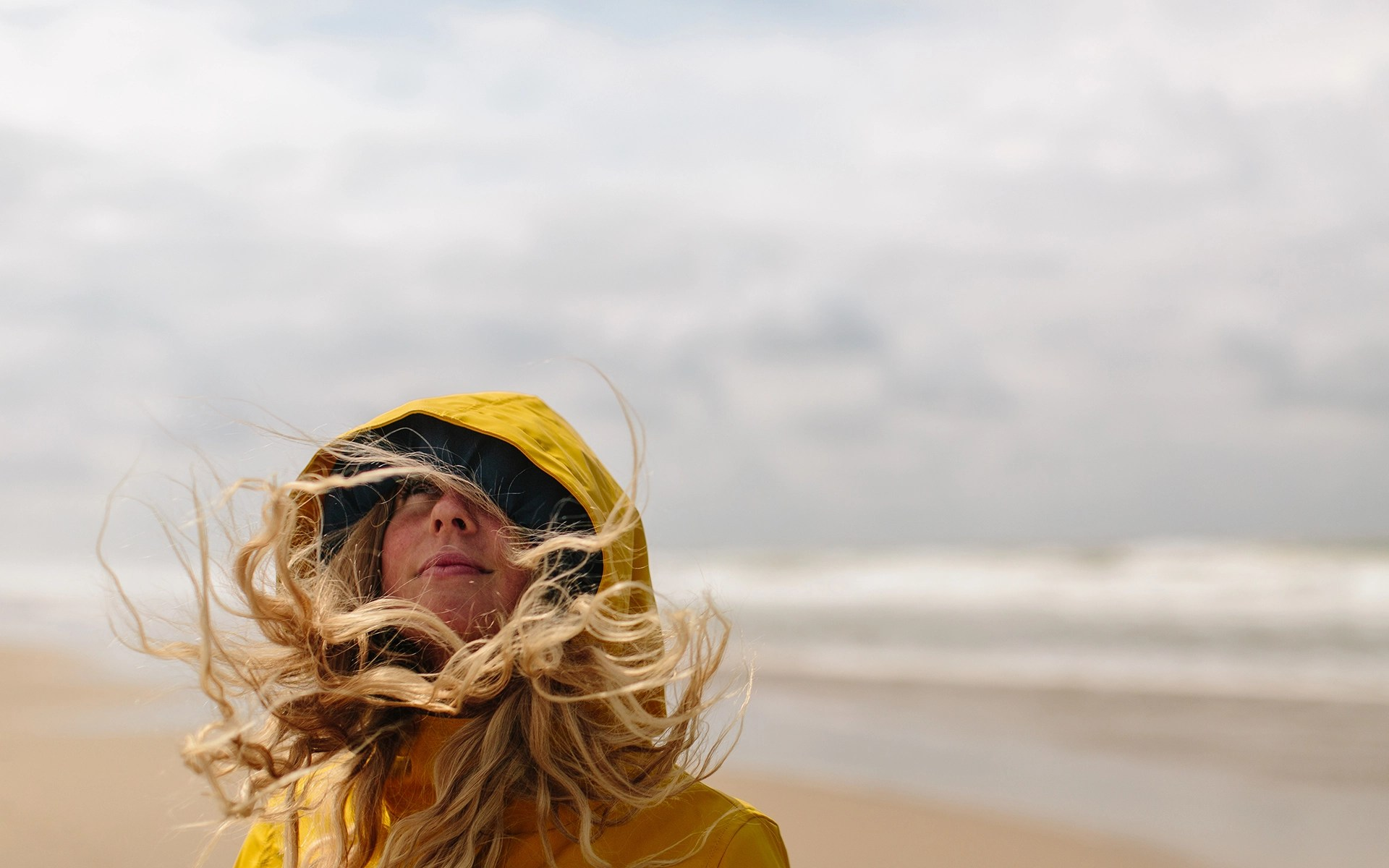A Blond Woman On A Windy Beach With Her Hair Blowing Everywhere.