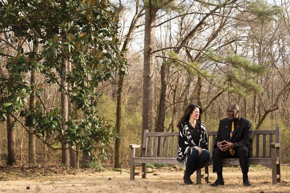 Elizabeth Paine and Don Cole sitting on bench together on fall day