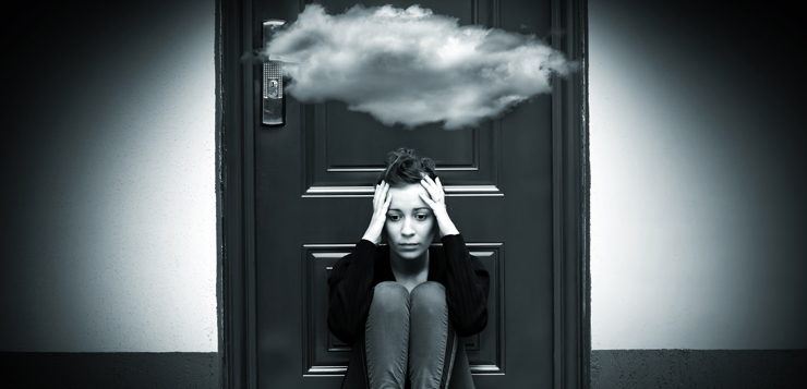 woman sitting on floor with cloud above her head