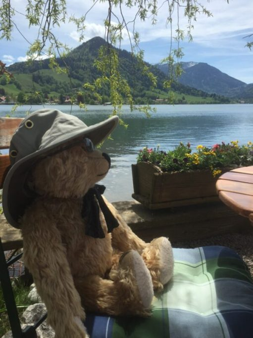 Bertie reclining in Schliersee Bavaria, looking across a lake wearing his Tilley 'at.