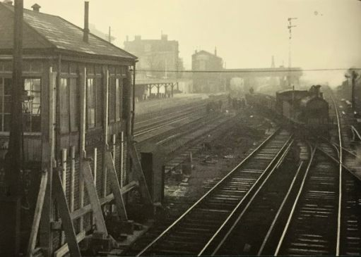 """The Footbridge: 1928 looking north before Wimbledon Station was completely rebuilt. The """"milk dock"""" is middle distance, behind the signal box in the foreground."""