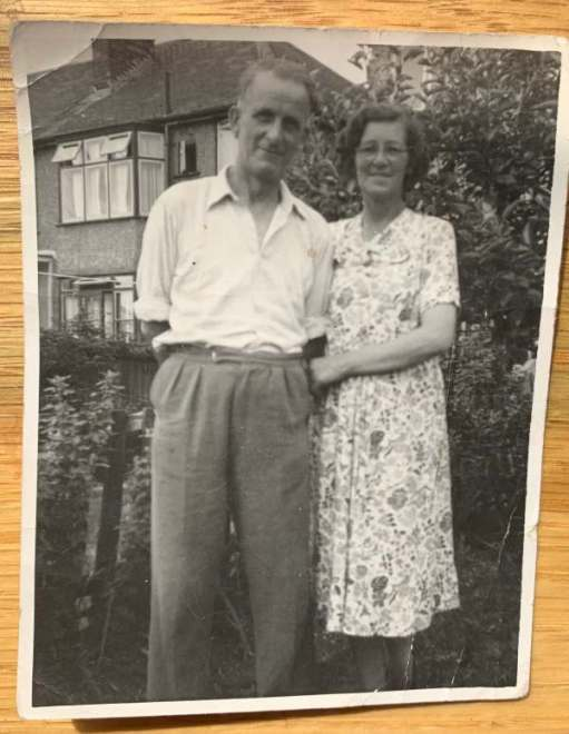 A black and white photograph ofSid and Dorothy in 1954(ish) standing arm in arm outside a semi-detached house.
