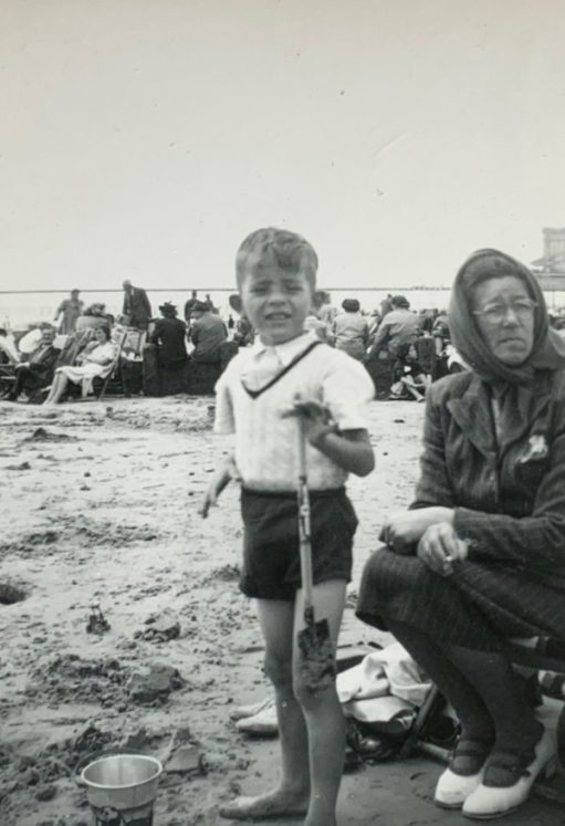 A black and white photo of a young Bobby standing on a beach alongside his mother, who is sat to his right,