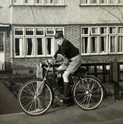 Bobby on a brand new bike outside his house. He is wearing his school uniform, complete with cap.