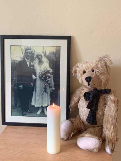 Bertie sat behind a large candle lit for Diddley. A framed picture of Bobby's parents on their wedding day in 1925 is next to Bertie.