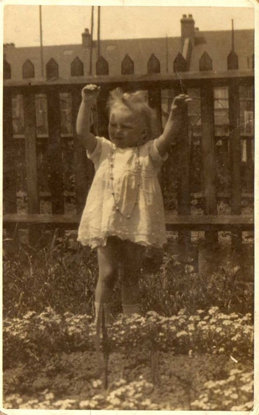 Picture of Doris, as a young child, playing outside in a garden.