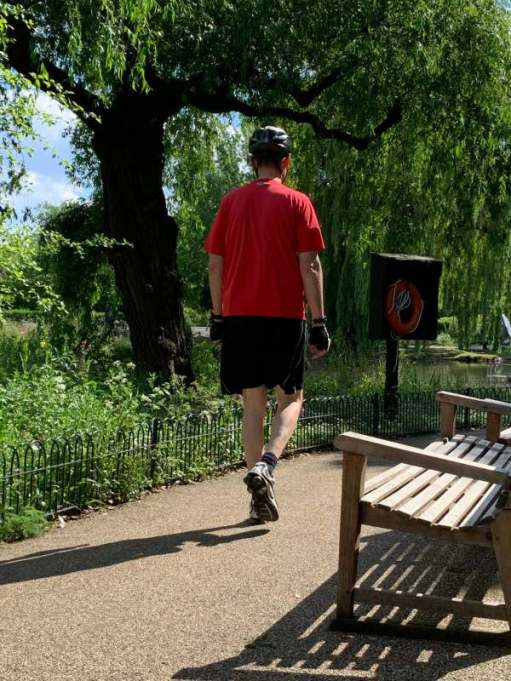 A man walking along the path by the lake, but wearing full cycling kit.