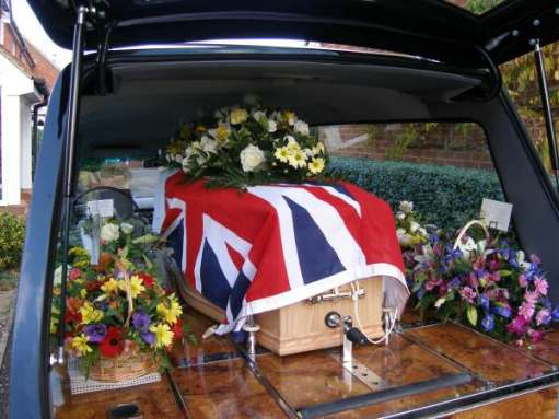 Tony's coffin in the hearse, covered with the White Ensign.