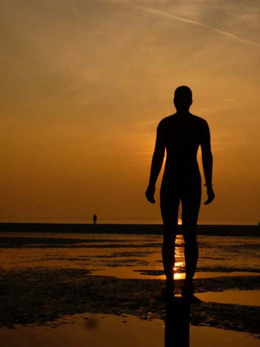 "Looking at the back of a Gormley statue on Crosby Beach ""Another Place"" against the setting sun. The sky is a deep orange colour and the setting sun is reflecting on the water between the statue's legs."